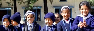 Young school children in India smiling and wearing hats to keep warm