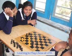 Young Indian children in school uniforms laughing and playing Chess