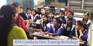 A group of Indian adolescent school children sitting in a classroom and listen to two women teachers