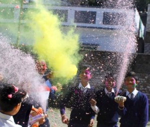 Indian children in blue and white school uniforms spray coloured powder at each other to celebrate Holi