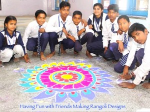 A group of Indian adolescent school children in blue and white uniforms around a colourful design made out of flour on the floor