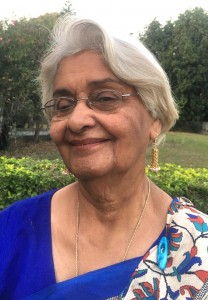 An elderly Indian woman with white hair in a sari smiles at the camera