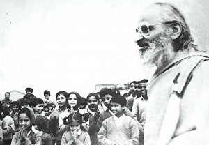 Black and white photo of smiling Indian man with a beard in profile. He is surrounded by young Indian children and a few adults