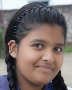 An adolescent Indian girl smiles at the camera