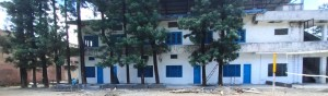 White, two story school building in India, with tall trees in front of it