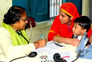 Three Indian people - a woman doctor, a mother wearing a red head covering, and a small boy - discussing health concerns