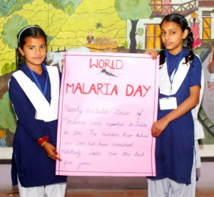 Two Indian school girls in blue and white salwar kameez uniforms hold up a sign saying 'World Malaria Day'