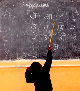 A small Indian boy uses a stick to reach up to point at Hindi letters written in white on a black chalkboard
